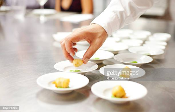 USA, New York City, Brooklyn, close up of chef's hand putting appetizers on plates