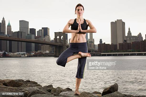 USA, New York City, Brooklyn, mature woman standing in yoga pose on river bank, portrait
