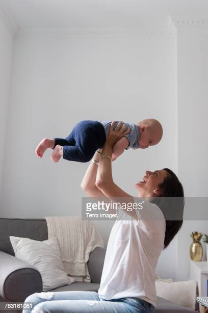 new york city, brooklyn, mom lifting baby boy (6-11 months) over her head - 6 11 months stock pictures, royalty-free photos & images
