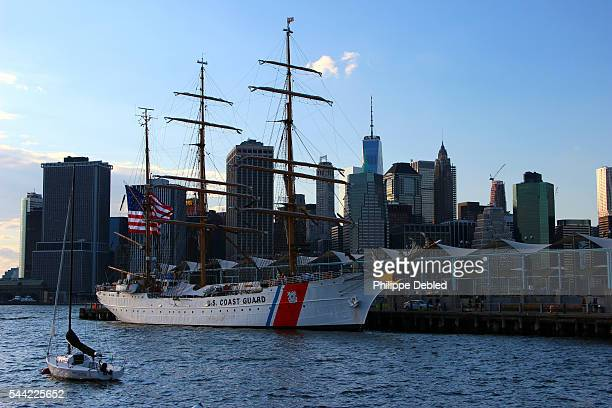 USA, New York City, Brooklyn, The U.S Coast Guard cutter Eagle at Pier 5 of Brooklyn Bridge Park and Lower Manhattan at the background