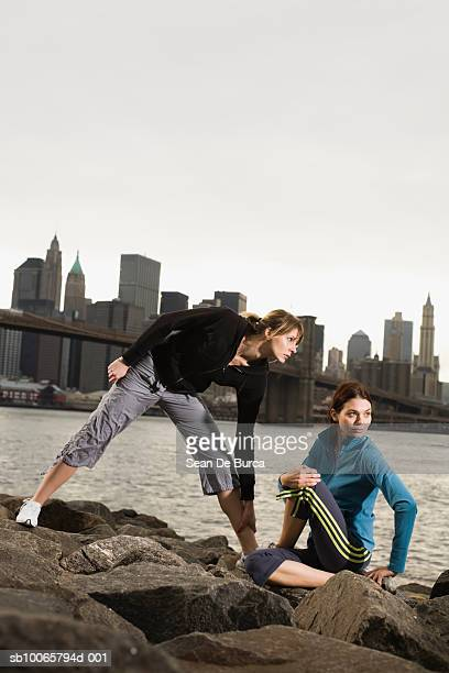 USA, New York City, Brooklyn, two young women stretching on river bank