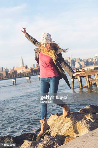 usa, new york city, brooklyn, williamsburg, blond woman stepping on stones by river, skyline in background - overcoat stock pictures, royalty-free photos & images