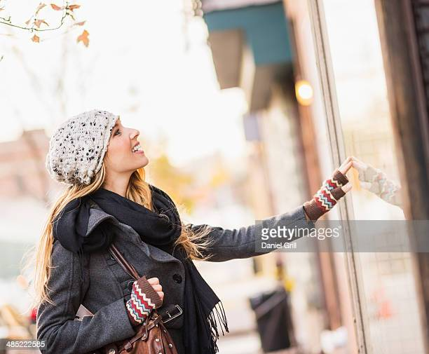 USA, New York City, Brooklyn, Williamsburg, Portrait of blond woman looking at window display