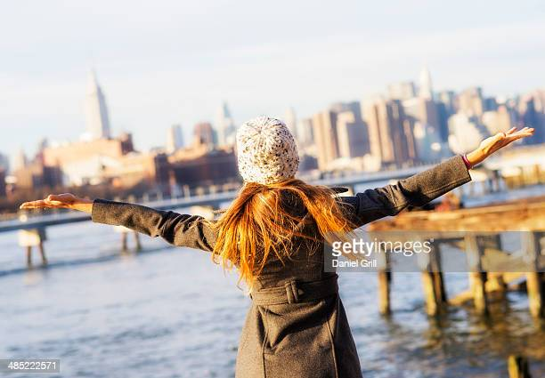 USA, New York City, Brooklyn, Williamsburg, Rear view of blond woman with arms outstretched