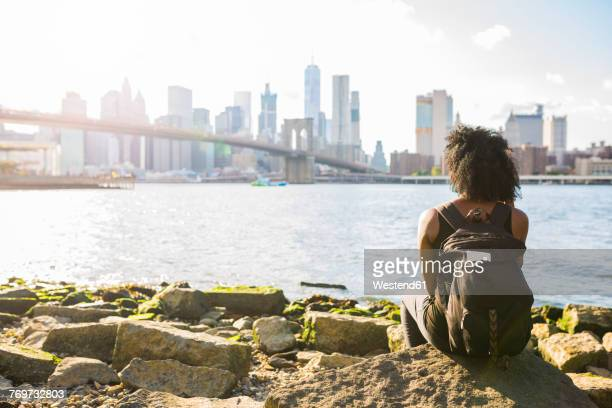 USA, New York City, Brooklyn, woman sitting at the waterfront