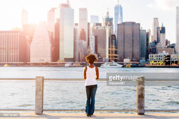 usa, new york city, brooklyn, woman standing at the waterfront looking at the skyline - parapetto barriera foto e immagini stock