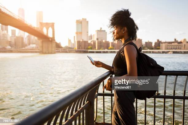 usa, new york city, brooklyn, woman with cell phone standing at the waterfront - afro amerikaanse etniciteit stockfoto's en -beelden