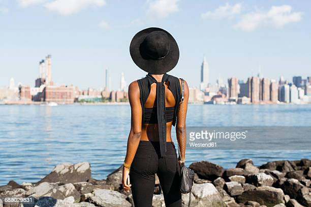 usa, new york city, brooklyn, young woman standing at east river - fashions hats and handbags stock pictures, royalty-free photos & images