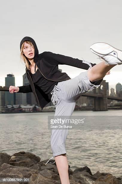 USA, New York City, Brooklyn, young woman training kick boxing on river bank
