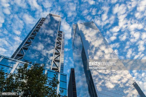 new york city buildings reflecting cloudy blue sky - monument stock pictures, royalty-free photos & images