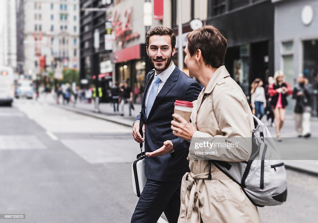 USA, New York City, businessman and woman walking in Manhattan : Stock Photo