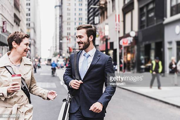 USA, New York City, businessman and woman walking in Manhattan