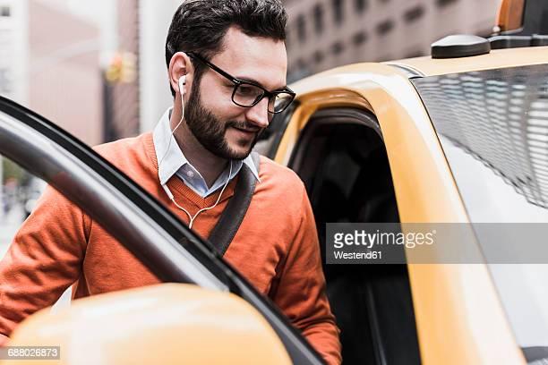 USA, New York City, Businessman entering cab