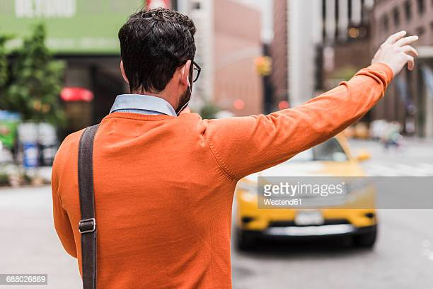 USA, New York City, Businessman hailing cab