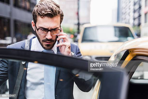 usa, new york city, businessman in manhattan on cell phone entering a taxi - 入る ストックフォトと画像