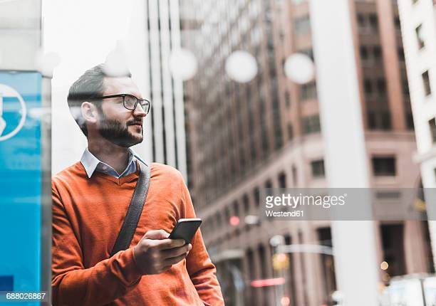 USA, New York City, Businessman leaning on ATM holding smart phone