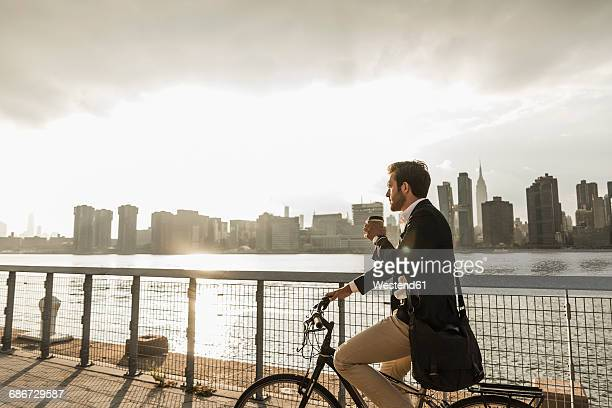 USA, New York City, businessman on bicycle with takeaway coffee