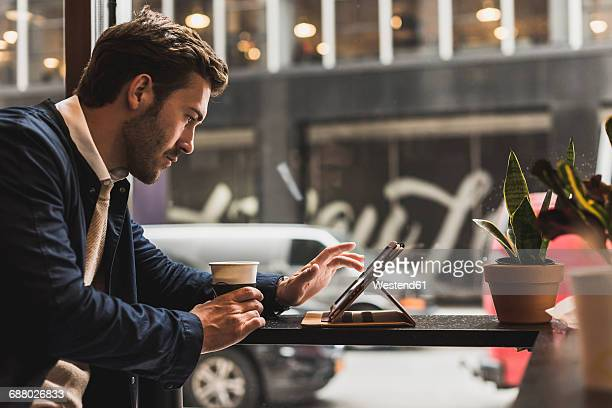 USA, New York City, Businessman sitting in coffee shop, using digital tablet