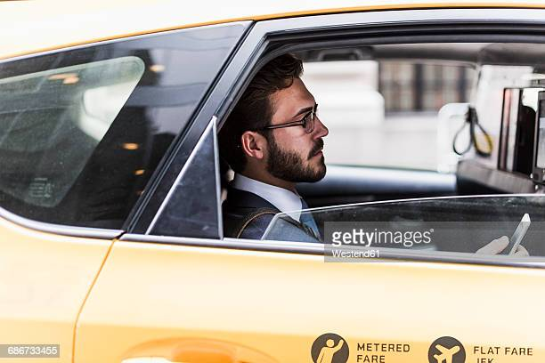 usa, new york city, businessman using cell phone in a taxi - イエローキャブ ストックフォトと画像