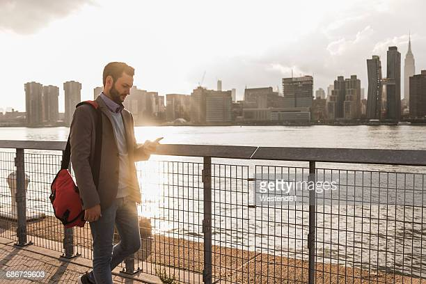 USA, New York City, businessman walking along East River looking at cell phone