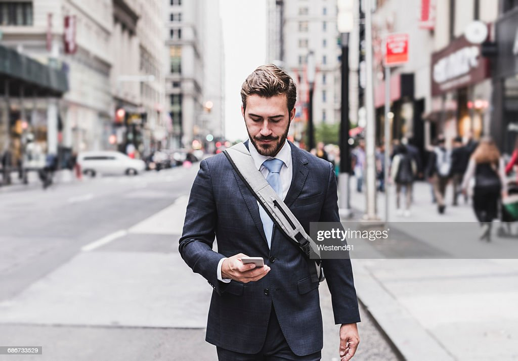 Usa New York City Businessman Walking In Manhattan Looking At Cell