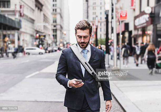 usa, new york city, businessman walking in manhattan looking at cell phone - man city stock photos and pictures
