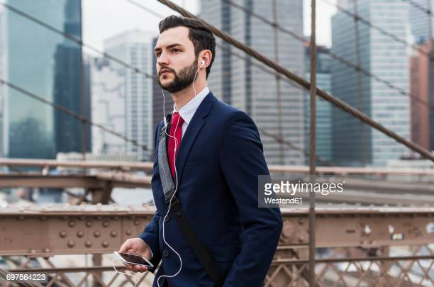 USA, New York City, businessman with cell phone and earbuds on Brooklyn Bridge