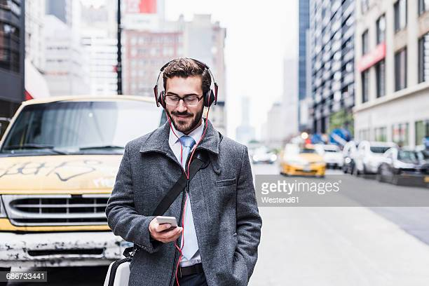 USA, New York City, businessman with cell phone and headphones on the go
