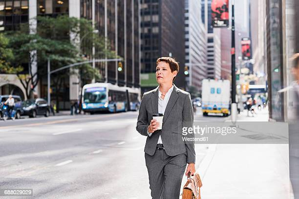 USA, New York City, businesswoman in Manhattan with takeaway coffee