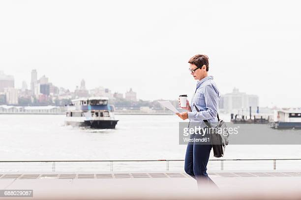 USA, New York City, businesswoman walking at East River reading document