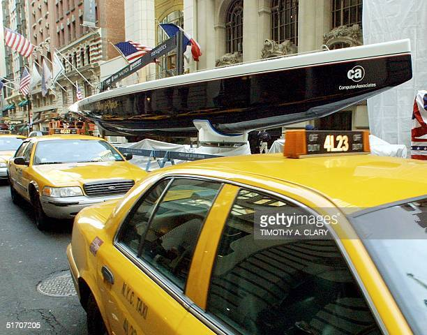 New York City cab passes before an unveiling by fourtime America's Cup champion Dennis Conner of his team's newest navy blue 79foot yacht Stars...