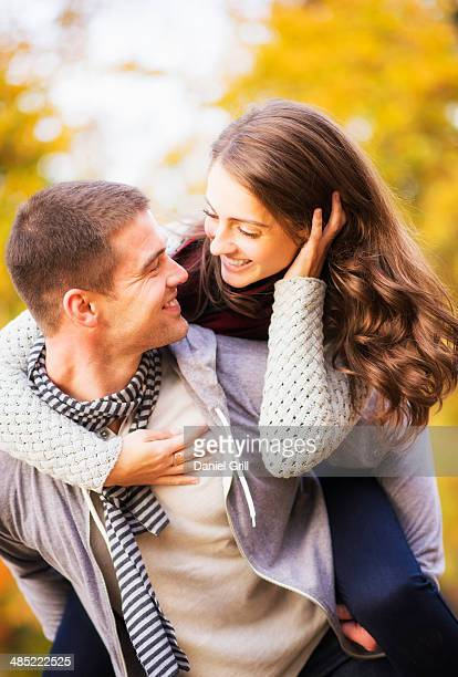 USA, New York City, Central Park, Man giving piggy back ride to woman in park