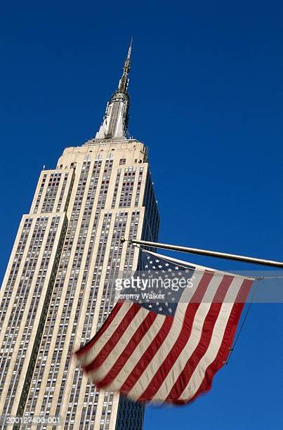 USA, New York City, Empire State Building and US flag, low angle view