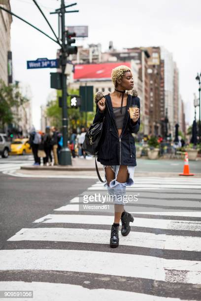 USA, New York City, fashionable young woman with coffee to go crossing the street