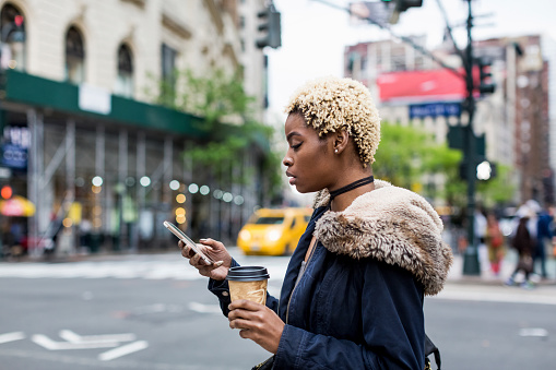 USA, New York City, fashionable young woman with coffee to go looking at cell phone on the street - gettyimageskorea