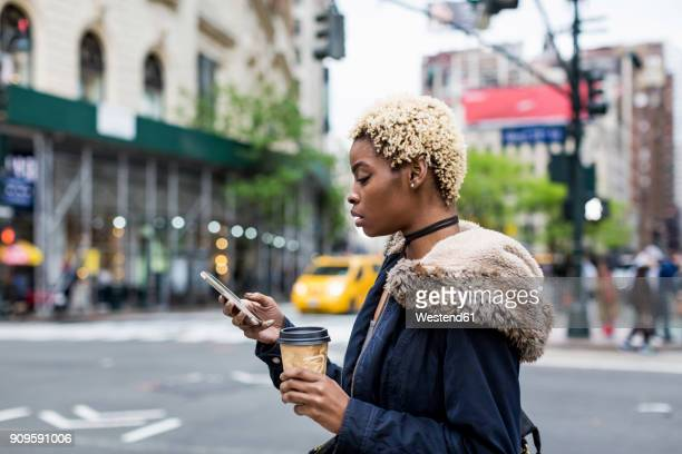 usa, new york city, fashionable young woman with coffee to go looking at cell phone on the street - black jacket stock pictures, royalty-free photos & images