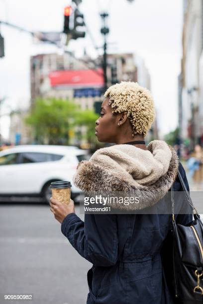 USA, New York City, fashionable young woman with coffee to go waiting at roadside