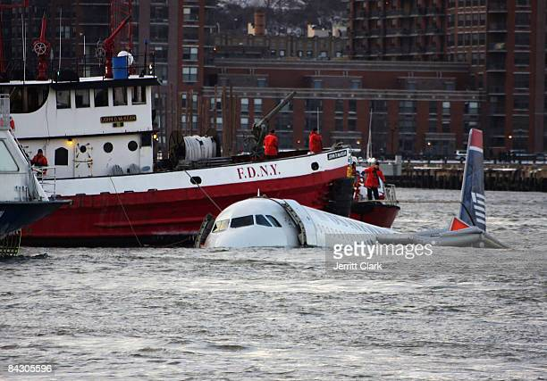 New York City Fire Department boat floats next to a US Airways plane floating in the water after crashing into the Hudson River in the afternoon on...
