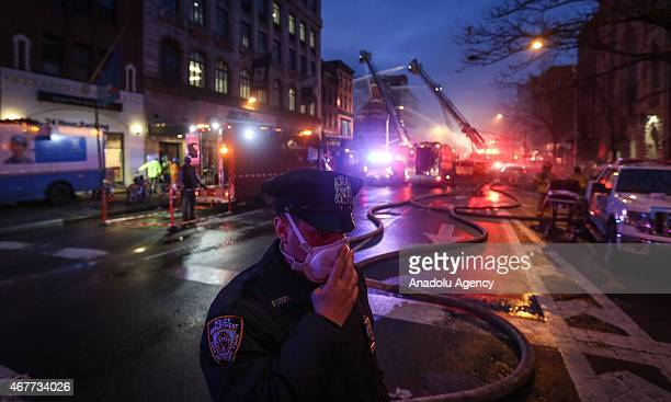New York City Fire Department personel try to extinguish the fire broke out after a massive explosion in a building on 2nd Avenue of Manhattan's East...
