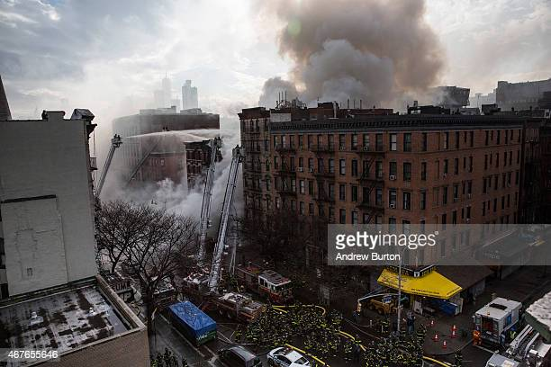New York City Fire Department personel work to extinguish a fire as a building burns after an explosion on 2nd Avenue of Manhatten's East Village on...