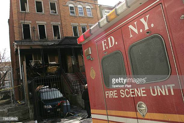 New York City Fire Deptartment vehicle is parked outside a burned out building March 8 2007 in the Bronx borough of New York City The lare night fire...