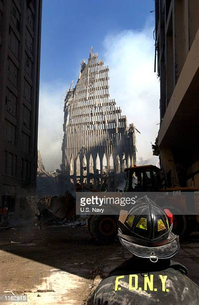 New York City fire fighter looks up at what remains of the World Trade Center September 13 2001 after its collapse following a September 11 2001...