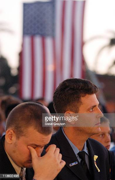 New York City Firefighter Bobby Senn comforts Chris Howard at the The 9/11 United In Memory Quilt Unveiling and Ceremony