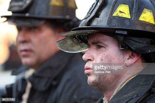 New York City firefighter, his face covered in soot, relaxes after battling a three-alarm fire on April 27, 2009 in the Brooklyn borough of New York...