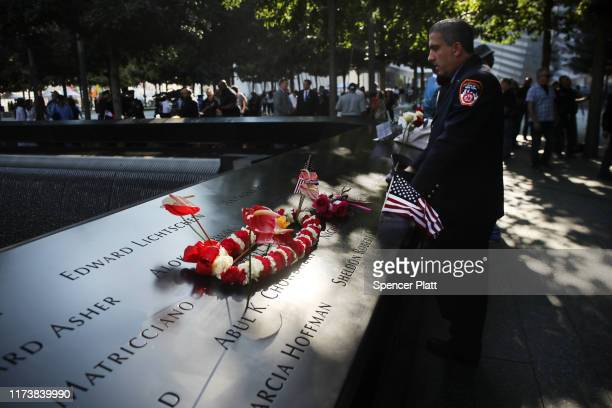 New York City firefighter observes a moment of silence during ceremonies at the National September 11 Memorial on September 11 2019 in New York City...