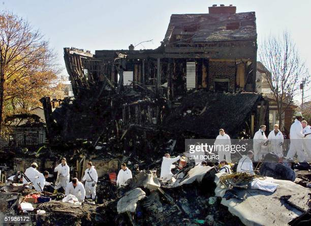 New York City firefighters in protective gear clear debris 14 November 2001 following the crash of American Airlines flight 587 in the Rockaway Beach...