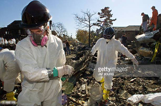 New York City firefighters in protective gear retrieve parts of American Airlines flight 587 from the pit at the corner of Beach 131st street and...