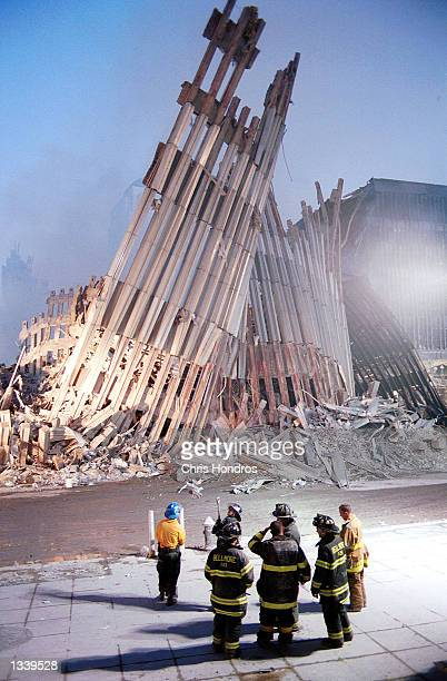 New York City firefighters look at the destroyed facade of the World Trade Center September 13 two days after the twin towers were destroyed when hit...