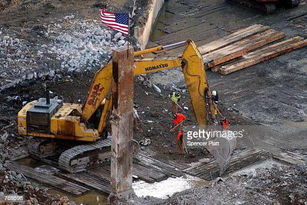 New York City firefighters police and other workers search the debris field March 27 2002 at the site of the World Trade Center terrorist attacks in...