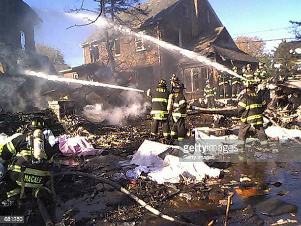 New York City firefighters remove bodies from the wreckage of American Airlines flight 587 November 12 2001 in Rockaway Beach Queens after the...
